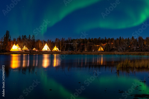 Foto auf Gartenposter Nordlicht Light up Tipi (indian Tent) with water reflection during Aurora Borealis (Northern Light) at Yellow Knife,