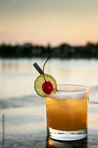 peach screwdriver mixed vodka cocktail drink outdoors at sunset