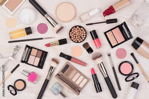 Obraz Makeup cosmetics such as eyeshadows, lipstick, mascara and makeup accessories on white, wooden background, top view - fototapety do salonu