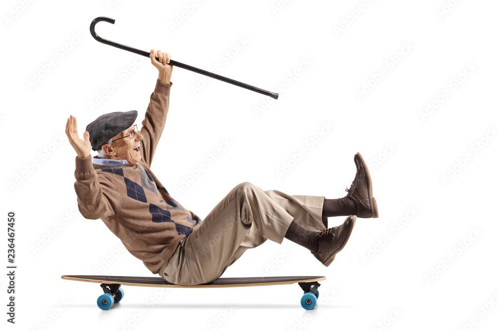 Fototapeta Cheerful senior with a cane sitting on a longboard and riding