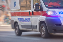 Paramedic 911 Ambulance Car Running Fast Through The Big City.