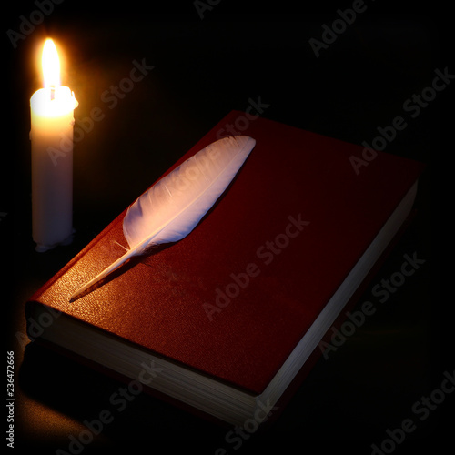 Valokuva  old book, burning candle and feather in the dark