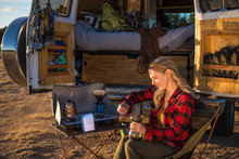 Smiling Woman Using Coffee Maker While Sitting On Chair By Motor Home At Campsite