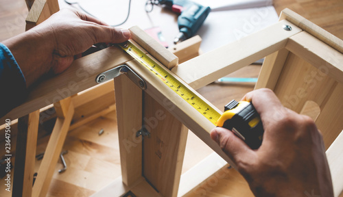 Photo  Man assembly wooden furniture,fixing or repairing house with tape measures