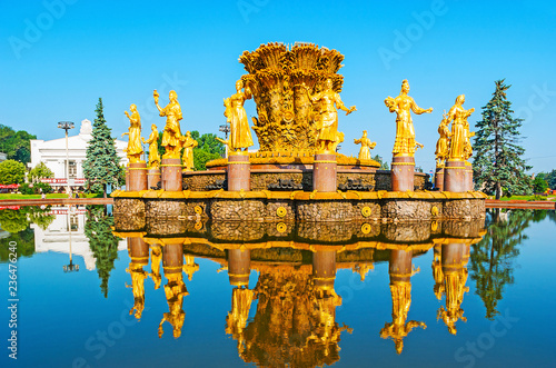 The splendid golden fountain of Friendship of Nations in former Soviet exhibition complex (VDNH) and its clear reflection in water, Moscow, Russia.