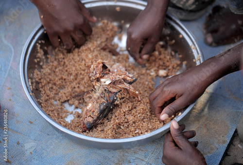 Valokuva  kids eating brown rice and fish in Africa - closeup