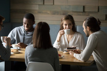 Happy Diverse Friends Having Fun In Coffeeshop Enjoying Coffee And Desserts, Smiling Multiethnic Young People Laughing At Joke, Spending Great Time Together In Cafe, Millennial Colleagues Meeting Out