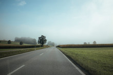 Diminishing Perspective Of Empty Road Amidst Green Landscape Against Sky