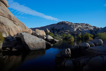 Scenic View Of Calm Lake Amidst Rock Formations Against Blue Sky At Joshua Tree National Park