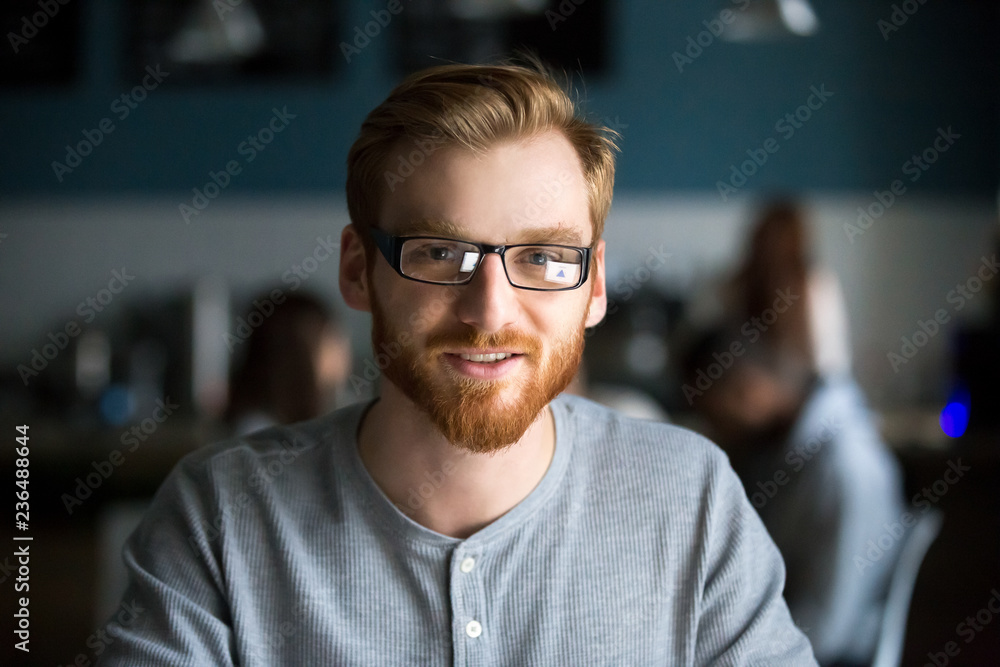 Fototapeta Portrait of smiling red haired millennial man looking at camera sitting in cafe or coffeeshop, happy young male in glasses posing for picture working at laptop or studying out in coffeehouse