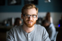 Portrait Of Smiling Red Haired Millennial Man Looking At Camera Sitting In Cafe Or Coffeeshop, Happy Young Male In Glasses Posing For Picture Working At Laptop Or Studying Out In Coffeehouse