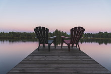 Two Adirondack Chairs Sitting On A Dock - Muskoka, Ontario, Canada.
