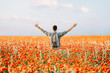 Leinwandbild Motiv Happy traveler man standing in poppies flowers meadow.
