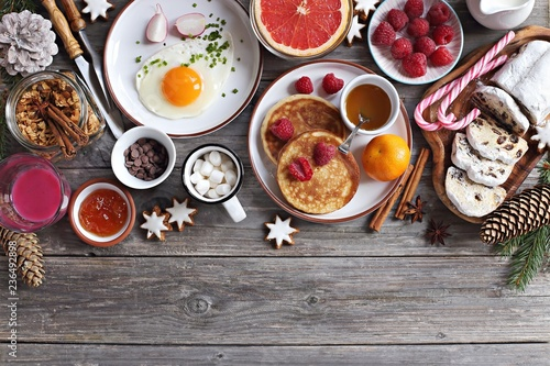 Christmas brunch or breakfast table. Festive brunch set, meal variety with fried egg, appetizers platter, pancakes, granola, smoothy and traditional sweets . Overhead view
