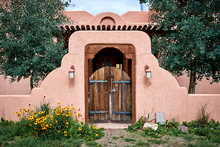 An Adobe Building With A Woode...