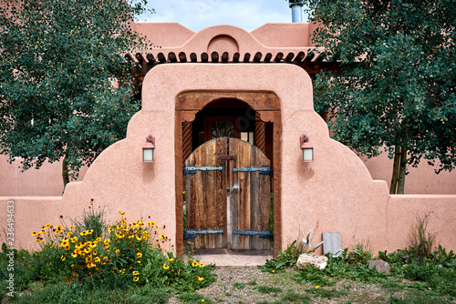 an adobe building with a wooden gate and wall Canvas Print