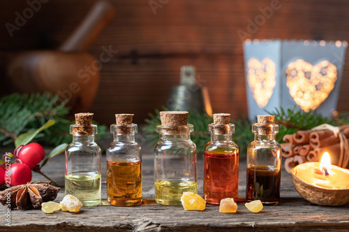 Fototapeta Christmas selection of essential oils with frankincense, wintergreen and star anise obraz