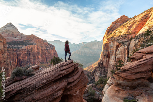 Canvas-taulu Adventurous Woman at the edge of a cliff is looking at a beautiful landscape view in the Canyon during a vibrant sunset