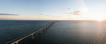 Aerial Panoramic View Of Confederation Bridge To Prince Edward Island During A Vibrant Sunny Sunrise. Taken In Cape Jourimain National Wildlife Area, New Brunswick, Canada.