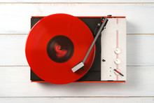Retro Turntable Vinyl Record Player On The Background White Wooden Boards. Sound Technology For DJ To Mix & Play Music. Needle On A Vinyl Record. Red Vinyl Record