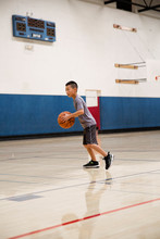 Boy Playing Basketball In An Indoor Gym