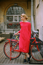 Young Pretty Woman Wearing Red Dress Standing Netx To Red Bicycle