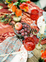 Wedding Table Setting In Red Colours With Candles, Fruits, Vases, Glasses And Flowers Made In Bohemian Style