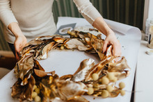 A Woman Making A Christmas Wreath Out Of Golden Leaves