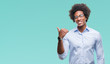 Leinwanddruck Bild - Afro american business man wearing glasses over isolated background smiling with happy face looking and pointing to the side with thumb up.