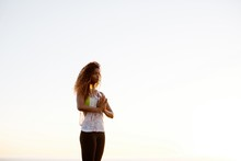 Fit, Stylish Woman Practicing Yoga At Sunset On Grass