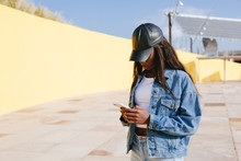 Black Woman Wearing Denim Clothes Using Her Phone On The Street.