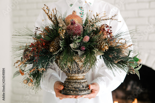 Woman hand holding beautiful vintage frosty Christmas decoration