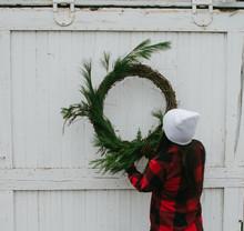 Young Woman Hangs Festive Holiday Wreath On Barn Door