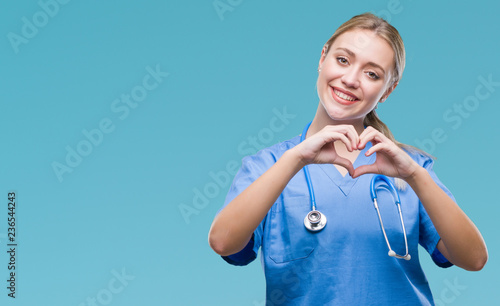Fotografía Young blonde surgeon doctor woman over isolated background smiling in love showing heart symbol and shape with hands