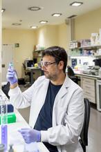 Male Scientist Using A Pipette In A DNA Laboratory