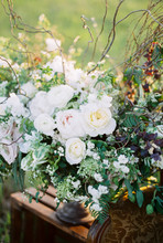 A Bouquet Of Green And White Flowers On Wooden Table