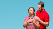 Middle age hispanic couple in love over isolated background smiling with hands on chest with closed eyes and grateful gesture on face. Health concept.