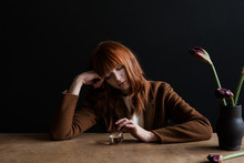Redhead Girl Sitting At Table