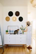 Woman Arranging Flowers On Dresser In Bedroom
