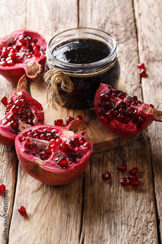 Delicious spicy pomegranate sauce narsharab with spices for seasoning meat dishes close-up. vertical