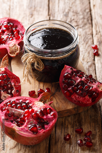 Fotobehang Aromatische Narsharab sauce of pomegranate juice and spices for seasoning meat dishes close-up. vertical
