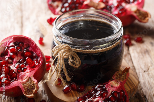 Azerbaijani seasoning Narsharab sauce made from pomegranate juice in a jar close-up. horizontal