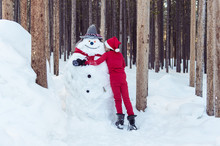 Child Hugging His Snowman In Morning Light
