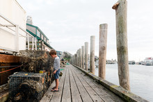 Little Boy Looking At Lobster Traps At A Seaport
