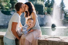 Young Lovely Couple With Little Son Kissing By The Fountain In Backlit
