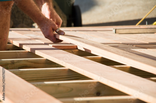 Fototapeta Man placing a plank of wood in a deck home renovation obraz