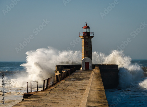 Photo sur Toile Phare lighthouse with a big wave of water from the ocean with blu sky
