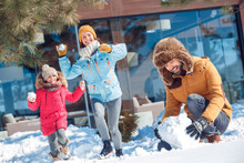 Winter Vacation. Family Time Together Outdoors Man Making Snowball For Fight While Woman And Girl Running Towards To Hit Him Smiling Cheerful