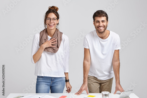 Fotografía  Shot of happy colleagues rejoice praise from boss for good job, have toothy smiles, stand near desk with tablet, glass of water and books, isolated over white studio background