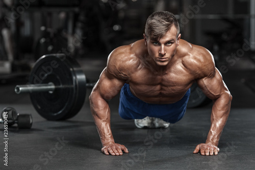 Fotografía  Muscular man working out in gym doing push-ups exercises, strong male naked tors